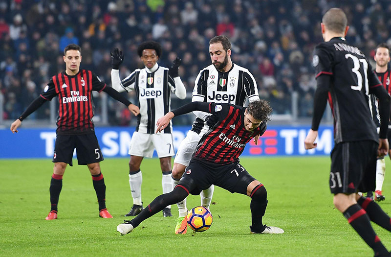 Juventus' Gonzalo Higuain challenges AC Milan's Manuel Locatelli during the Italian Cup, Round of 8 soccer match between Juventus and AC Milan, at the Juventus stadium in Turin, Italy, on Wednesday, January 25, 2017.  Photo: Alessandro Di Marco/ANSA via AP