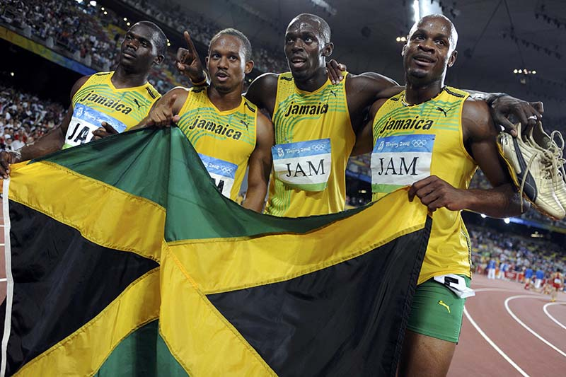 File-(From right) Asafa Powell, Usain Bolt, Michael Frater and Nesta Carter of Jamaica celebrate after winning the final of the athletics competition in the National Stadium during the Beijing 2008 Olympic Games on August 22, 2008. Photo: Reuters