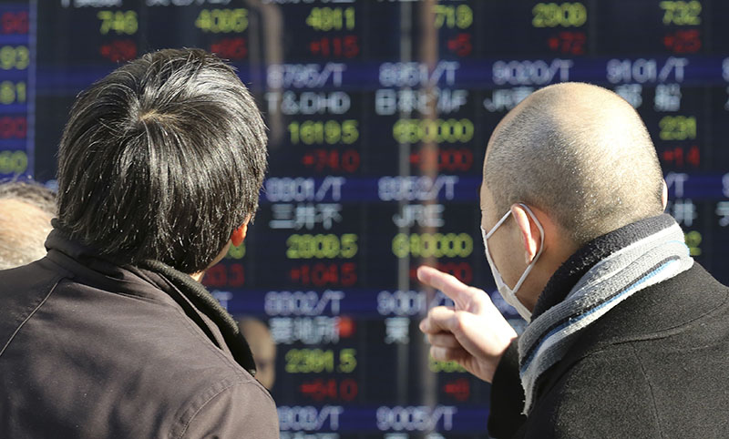 People look at an electronic stock board of a securities firm in Tokyo, on Wednesday, January 4, 2017. Photo: AP