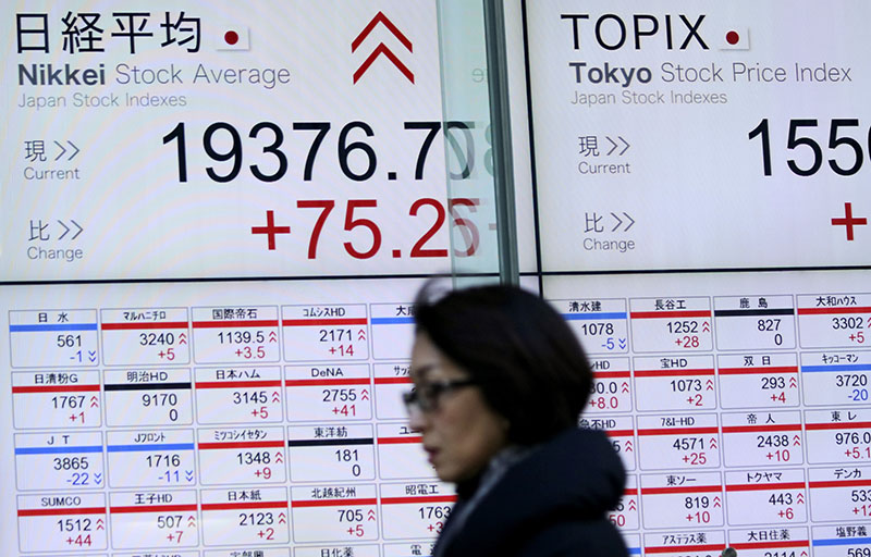 A woman walks past an electronic stock board showing Nikkei stock index at a securities firm in Tokyo, on Wednesday, January 11, 2017. Photo: AP