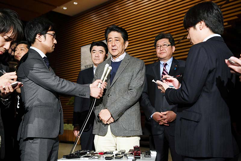 Japanese Prime Minister Shinzo Abe (centre) talks to reporters after having a phone conversation with US President Donald Trump, at his official resident in Tokyo, Japan, on January 28, 2017.  Photo: Kyodo via Reuters