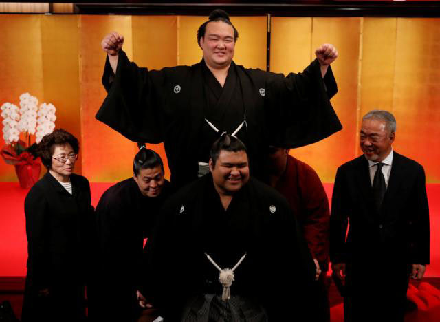 Japanese sumo wrestler Kisenosato (top centre) raises his arms as he is hoisted up by his stable's sumo wrestlers in celebration of his promotion to Yokozuna, or grand champion, after a ceremony in Tokyo, Japan, on January 25, 2017. Kisenosato's parents ,Sadahiko Hagiwara (right) and Yumiko (left) look on. Photo: Reuters