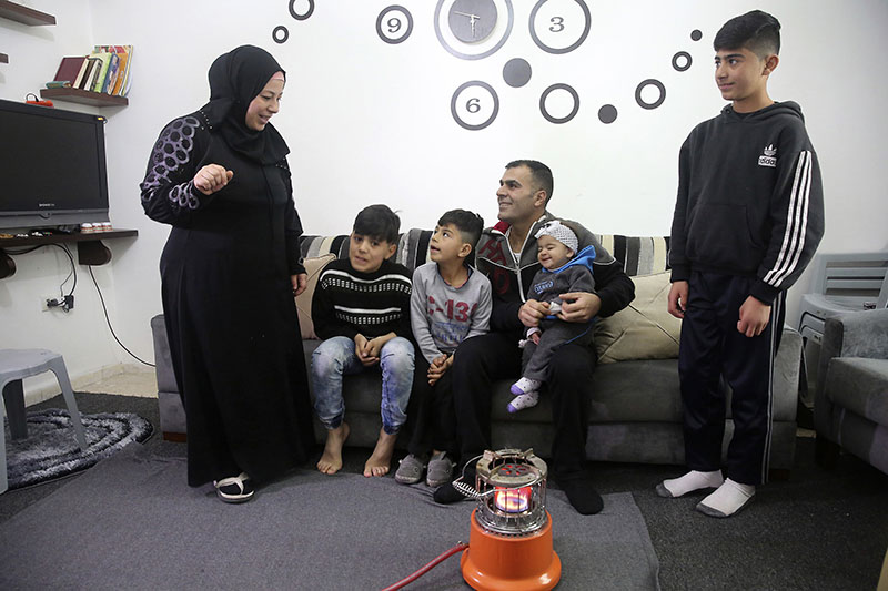 The Sawan family from Moadamiyeh, outside Damascus talk in front of a gas heater in their home in Amman, Jordan, on Saturday, January 28, 2017, the day the family learned they won't be headed to the US after American President Donald Trump's executive order to indefinitely halt all Syrian refugee immigrations. Photo: AP