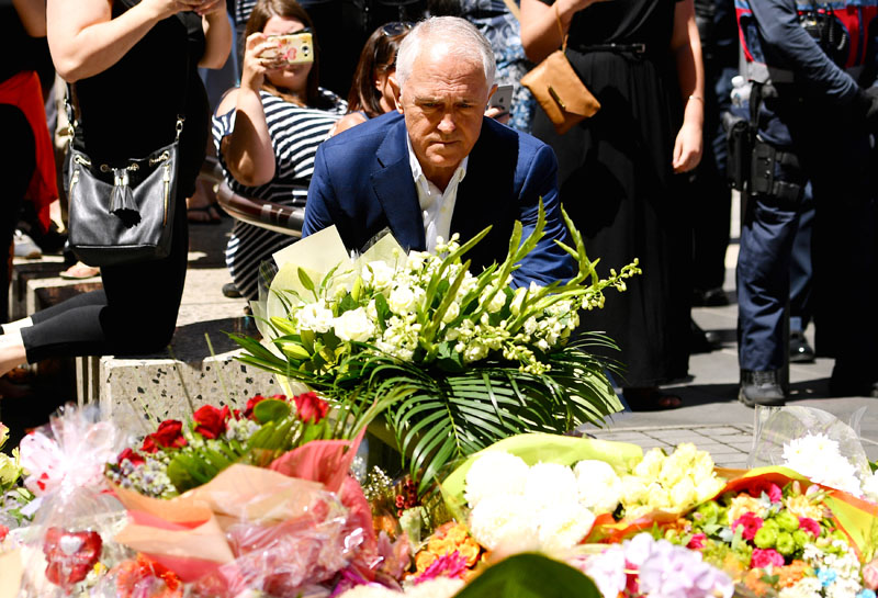 Australian Prime Minister Malcolm Turnbull lays a floral tribute in central Melbourne, Australia, on January 22, 2017 to the victims killed and injured when a man drove into pedestrians on Friday. Photo: AAP via Reuters