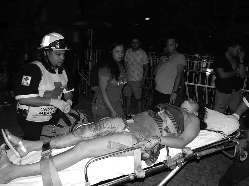 A first responder aids a woman wounded after a shooting at an electronic music festival in the Caribbean coast resort of Playa del Carmen, Mexico, on early Monday, January 16, 2017. Photo: Por Esto de Quintana Roo, via AP