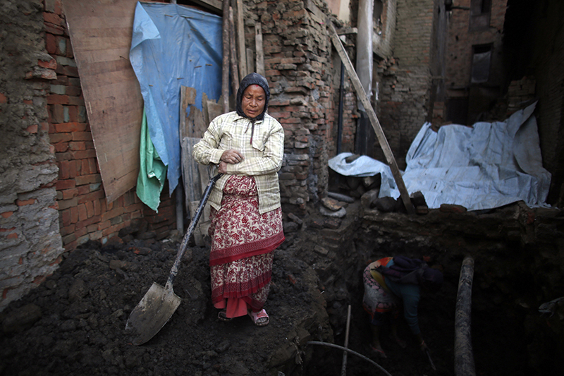 Nhuchhe Laxmi Prajapati holds a shovel as digs the foundation of her damaged house, in Bhaktapur, on Wednesday, January 4, 2017.