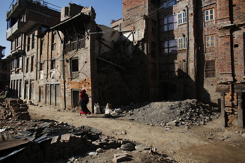 A woman walks past houses that were damaged in the 2015 earthquake in Bhaktapur, on Wednesday, January 4, 2017.