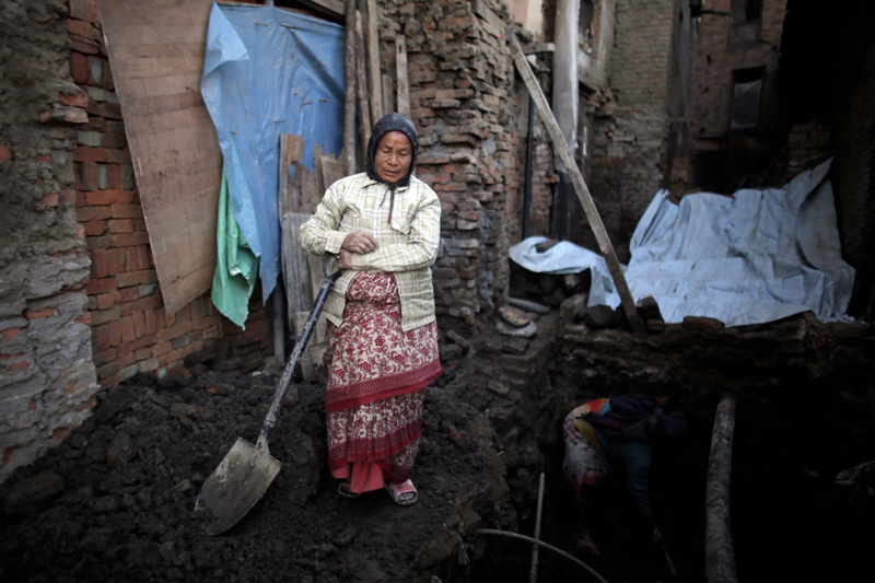 Nhuchhe Laxmi Prajapati holds a shovel as digs the foundation of her house which was damaged by the 2015 earthquake in Bhaktapur, on Wednesday, January 4, 2017. People who lost their homes in the devastating earthquake that hit Nepal nearly two years ago are tired of waiting for help to rebuild. Photo: AP