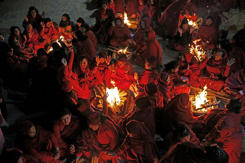 Nepali women warm themselves near a bonfire before taking a holy dip at the Shalinadi River, on the first day of the month-long Swasthani Brata Katha festival, at Sankhu in Kathmandu, on Thursday, January 12, 2017. Photo: Skanda Gautam/THT