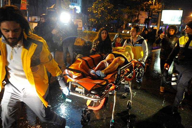 An injured woman is carried to an ambulance from a nightclub where a gun attack took place during a New Year party in Istanbul, Turkey, on January 1, 2017. Photo: Ihlas News Agency via Reuters