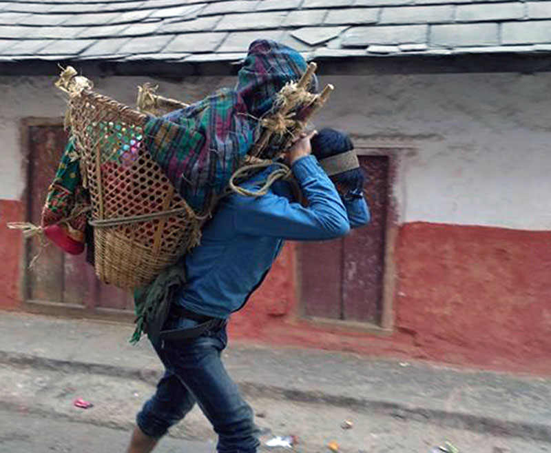 A sick woman is seen taken to a hospital by being carried on back in a doko (wicker basket) in Rolpa district on Thursday, January 5, 2017. Owing to the lack of transportation facilities, patients in the district are still taken to hospitals in this way. Photo: RSS