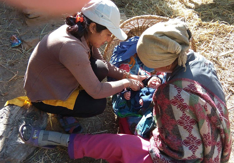 ANM Chitra Kumari Tamang of Phase Nepal helping a new mother and her baby at Wai VDC, in Bajura, on Wednesday, January 25, 2017. Photo: THT