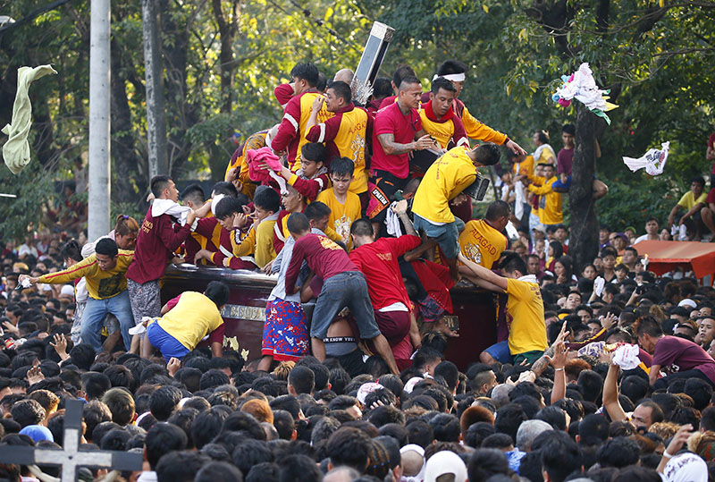 Filipino Roman Catholic devotees climb the carriage to kiss and rub with their towels the image of the Black Nazarene to celebrate its feast day, on Monday, January 9, 2017 in Manila, Philippines. Photo: AP