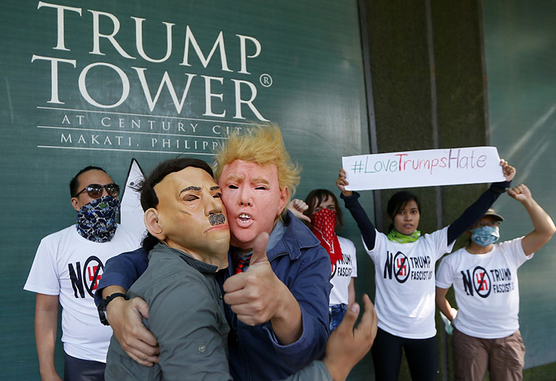 Protesters, one wearing a Donald Trump mask and another with an Adolf Hitler mask, embrace as others display a #lovetrumpshate hashtag during a brief picket at the Trump Tower hours after Trump was sworn in as the 45th President of the United States, on Saturday, January 21, 2017 in the financial district of Makati city east Manila, Philippines. Photo: AP