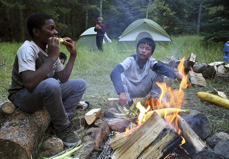 Justin Mbelechi (13) and Bidesh Magar (14) (right) roast corn at their campsite in Evergreen, Colorado, on September 10, 2016. The two belong to a Colorado Boy Scout troop that is made up almost entirely of refugees. At campouts, traditional American food like hot dogs and trail burgers is replaced by fish head stew, fire-roasted corn and Chatpate, a popular Nepali street snack. Photo: AP