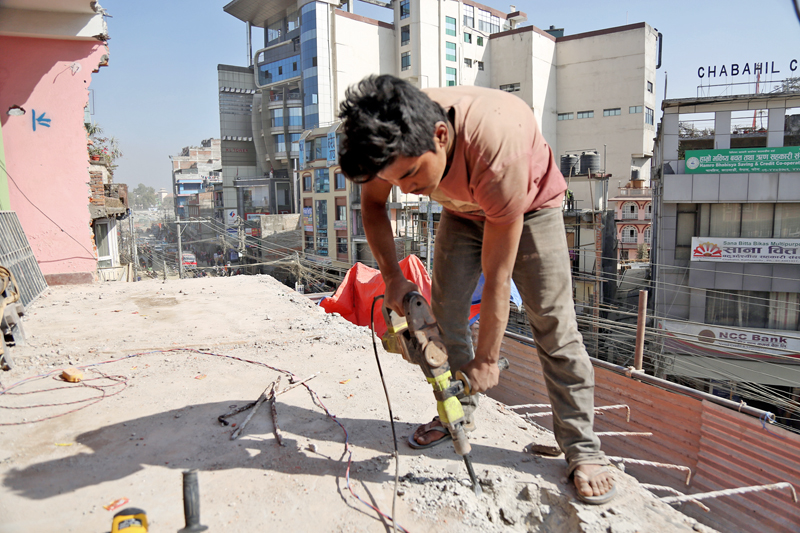 A labourer without any safety gear is seen demolishing a house along the Chabahil-Sankhu road section, in Kathmandu, on Monday, January 23, 2017. Photo: RSS