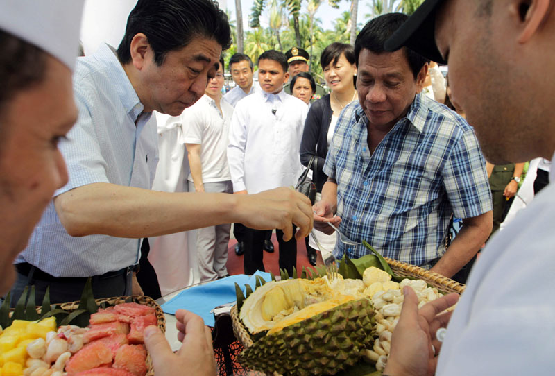 President Rodrigo Duterte and Japan's Prime Minister Shinzo Abe (left) try durian fruit after attending various events at the Waterfront Hotel in Davao City, southern Philippines, on January 13, 2017. Photo: Malacanang Photo via Reuters