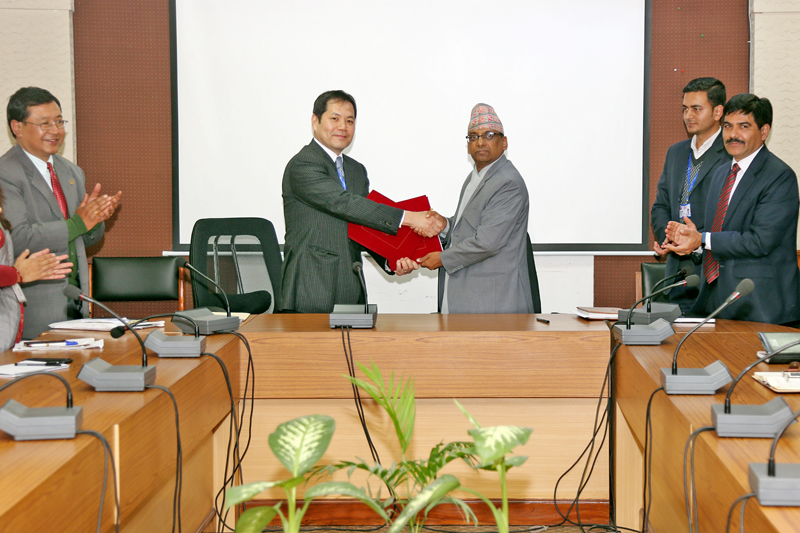 Finance Secretary Shantaraj Subedi (right) and World Bank Country Manager to Nepal, Takuya Kamata, exchange documents after signing an agreement on USD 150 million credit for a digitation project, at the Ministry of Finance in Kathmandu, on Monday, January 23, 2017. Photo: RSS
