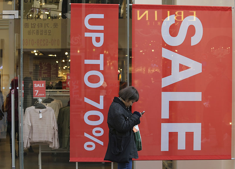 A woman uses her smartphone in front of sale signs at a shopping district in Seoul, South Korea, on Wednesday, December 28, 2016. Photo: AP
