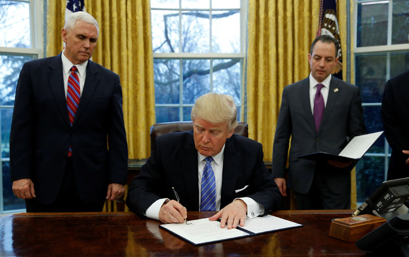 US President Donald Trump signs an executive order on US withdrawal from the Trans Pacific Partnership while flanked by Vice President Mike Pence (L) and White House Chief of Staff Reince Priebus (right) in the Oval Office of the White House in Washington on January 23, 2017. Photo: Reuters