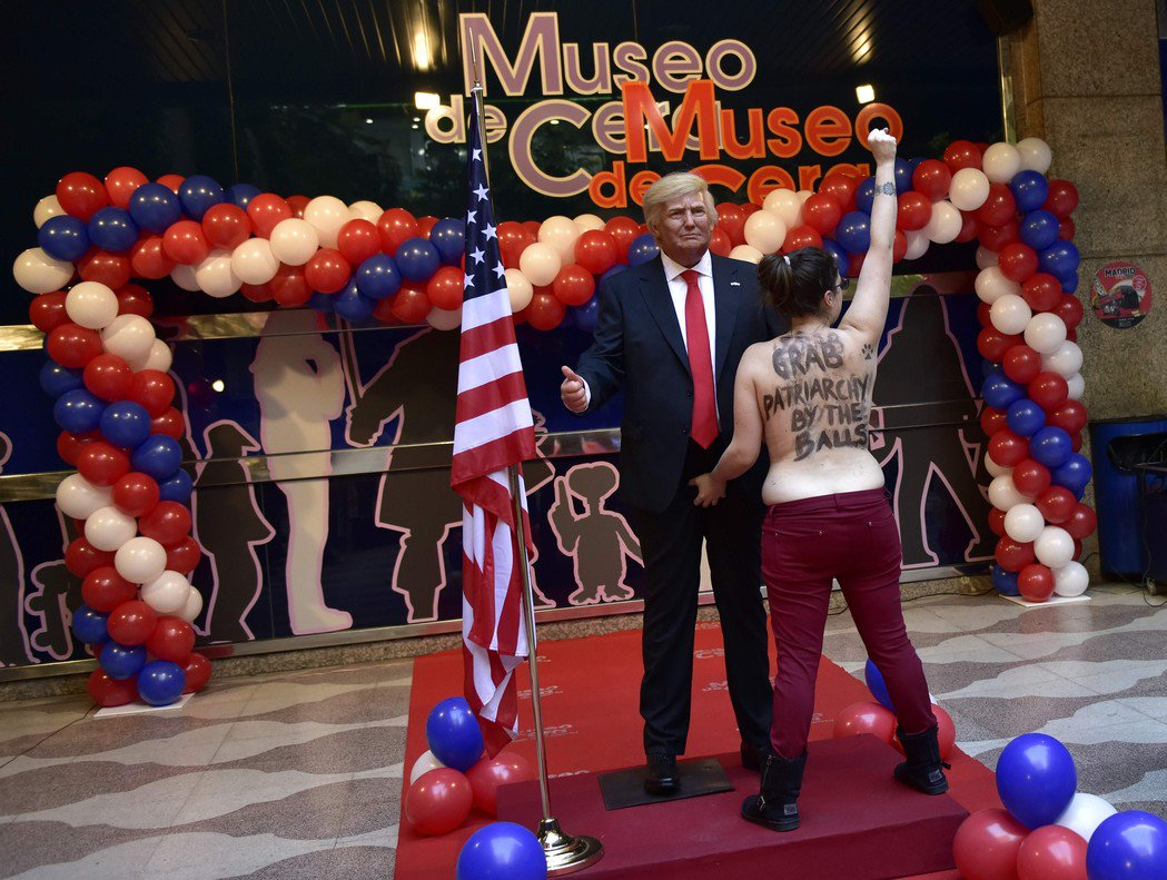 A FEMEN activist holding the crotch of Donald Trump's statue in a wax museum in Madrid. Photo: Twitter.com/@FemenSwe