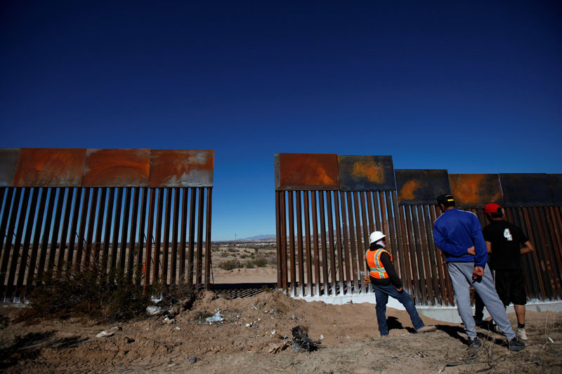 A worker chats with residents at a newly built section of the US-Mexico border fence at Sunland Park, US opposite the Mexican border city of Ciudad Juarez, Mexico, on January 26, 2017. Photo: Reuters