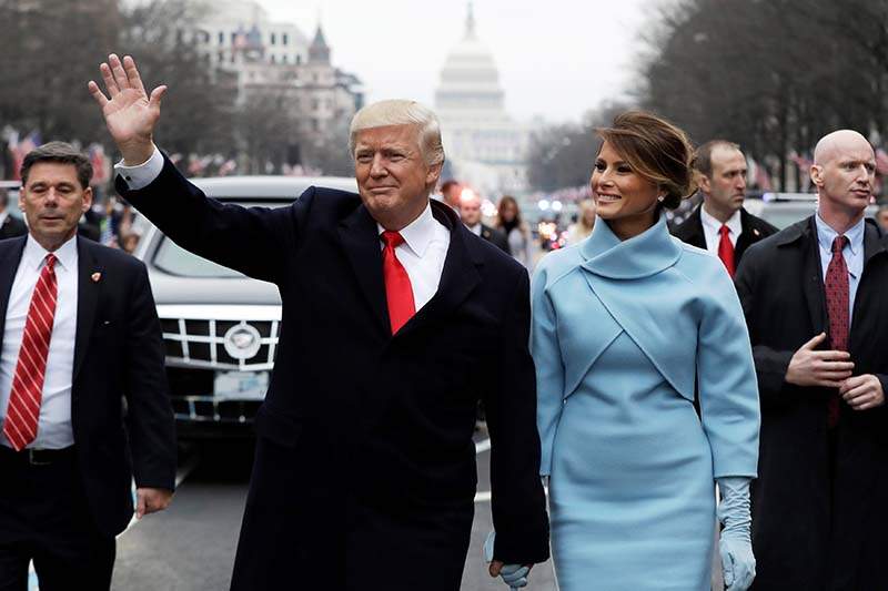 US President Donald Trump waves as he walks with first lady Melania Trump during the inauguration parade on Pennsylvania Avenue in Washington, on January 20, 2017. Photo: Reuters