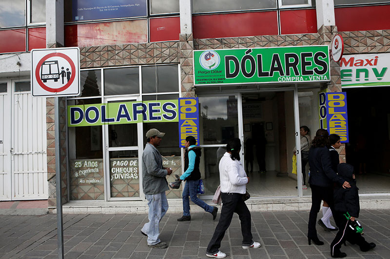 People walk past a foreign exchange building and a money transfer business in Ixmiquilpan , Mexico, on December 9, 2016. Photo: Reuters