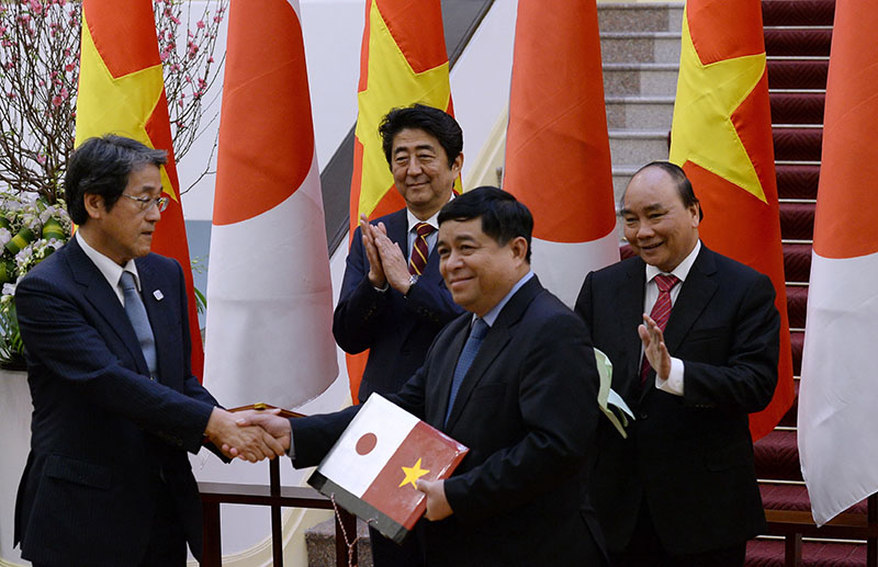 Japan's Prime Minister Shinzo Abe (second left) and his Vietnamese counterpart Nguyen Xuan Phuc (right) applaud as Vietnam's Planning and Investment Minister Nguyen Chi Dung (second right) and Japanese Ambassador to Vietnam Kunio Umeda exchange a signed agreement at Phuc's Cabinet Office in Hanoi, Vietnam, on Monday, January 16, 2017. Abe is on a two-day official visit to Vietnam. Photo: Hoang Dinh Nam/Pool Photo via AP