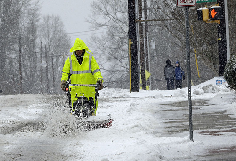A city worker removes snow from a crosswalk as a winter storm blankets the area in Carrboro, North Carolina, on Saturday, Janury 7, 2017.  Photo: AP