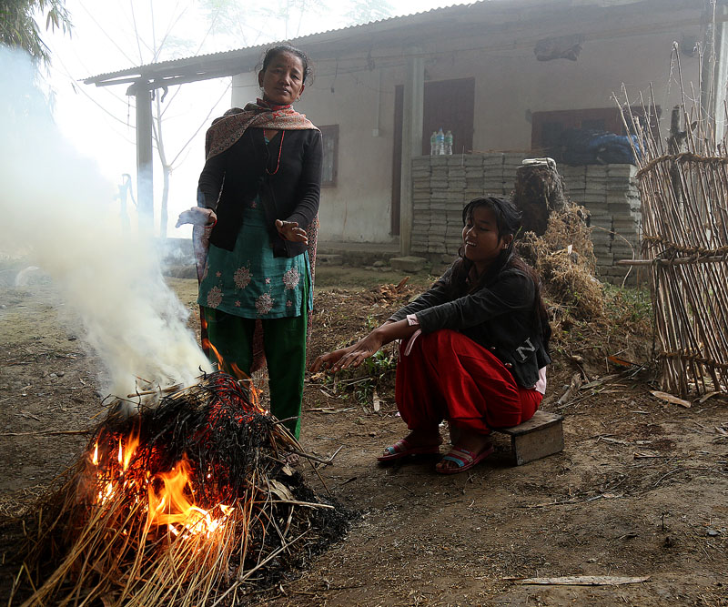 Women are seen warming their bodies by sitting nearby a fire, in Chitwan, on Sunday, January 1, 2017. Photo: RSS
