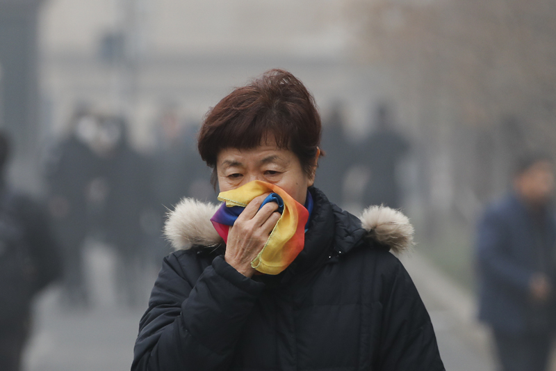 FILE - In this Tuesday, Dec. 20, 2016, file photo, a woman uses a scarf to cover her mouth for protection against the air pollution as she walks on a street in Beijing, China. Photo: AP