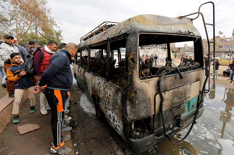 People look at a burned vehicle at the site of car bomb attack in a busy square at Baghdad's sprawling Sadr City district, in Iraq on January 2, 2017. Photo: Reuters