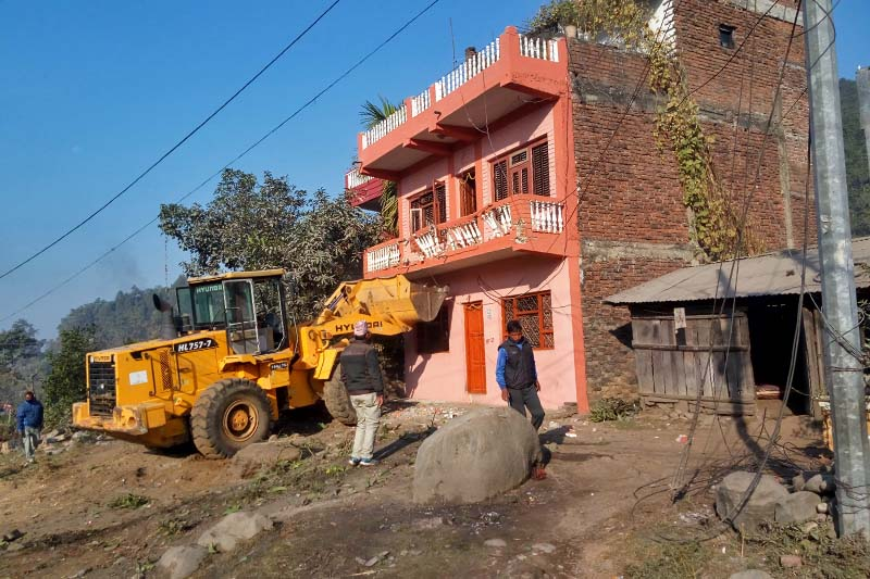 A bulldozer demolishes a house under the road widening project of the Division Road Office, Hetuanda, along the East-West Highway in Hetaunda, on Tuesday, January 17, 2017. Photo: Prakash Dahal/THT
