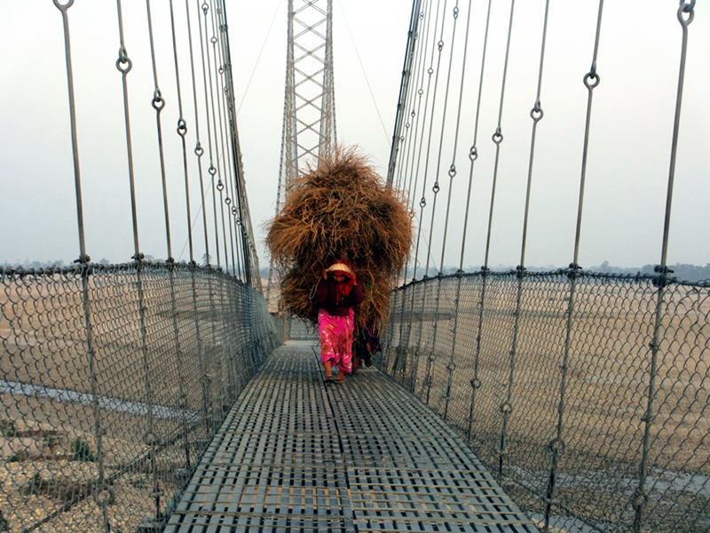 A local woman crosses the bridge over Mahakali River in Chandani Dodhara of Kanchanpur district, with a heap of hay on her back, in Kanchanpur district, on Saturday, January 14, 2017. Photo: RSS