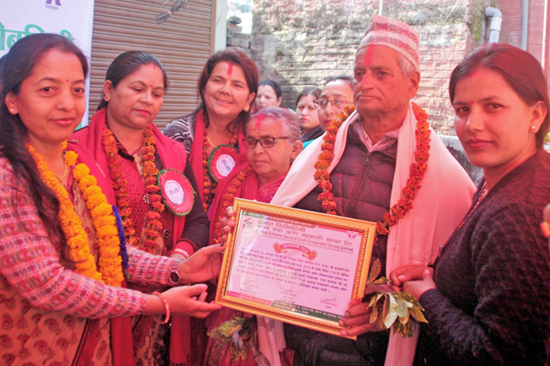 Members of a Chitwan-based local cooperative pose for a photo after honouring a senior citizen with a certificate on the occasion of its 22nd anniversary, in Bharatpur, on Thursday, January 19, 2017. Photo: RSS