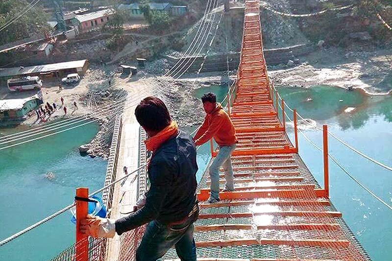 Workers stand on the under-construction bridge over the Dudhkoshi River at Jayaramghat, on Wednesday, January 18, 2017. AS much as 85 per cent of the construction work has been completed for the bridge connecting Khotang and Okhaldhunga districts. Photo: RSS