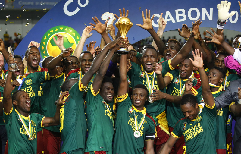 Cameroon's Benjamin Moukandjo celebrates with the trophy and teammates after winning the African Cup of Nations. Photo: Reuters
