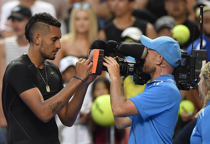 Australia's Nick Kyrgios signs his autograph onto the lens of a television camera after his win over Portugal's Gasto Elias in their first round match at the Australian Open tennis championships in Melbourne, Australia, on Monday, January 16, 2017. Photo: AP