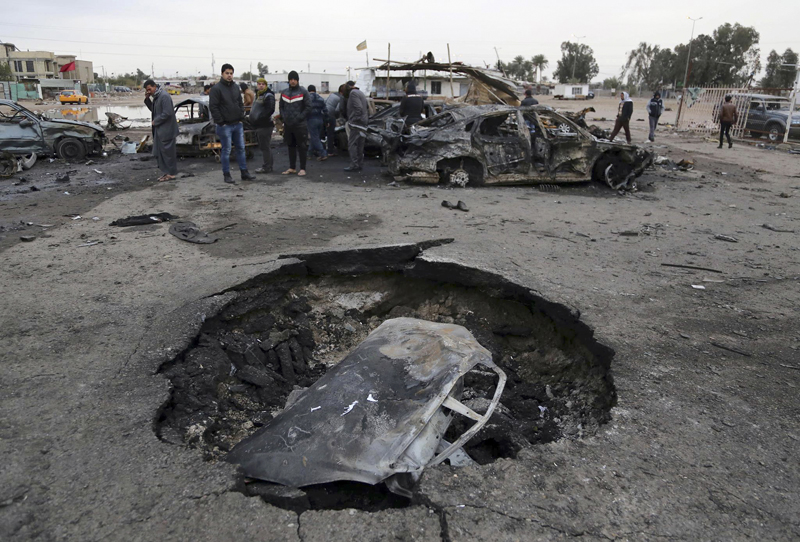 Civilians gather near a crater caused by a car bomb at a used car dealer's parking lot in the southwestern al-Bayaa neighborhood, Baghdad, Iraq, Friday, Feb. 17, 2017. Photo: AP