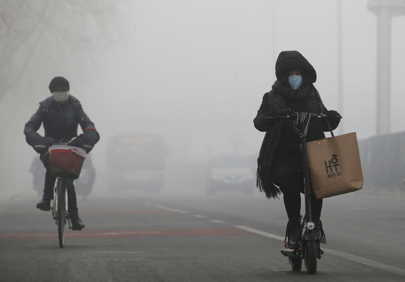 People ride amid the smog in Beijing, China, on February 14, 2017. Photo: Reuters