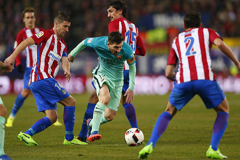 FC Barcelona's Leo Messi (centre) duels for the ball with Atletico de Madrid Gabriel Fernandez 'Gabi', left, during a Spanish Copa del Rey semifinal first round soccer match between Atletico de Madrid and FC Barcelona at the Vicente Calderon stadium in Madrid, Spain, on Wednesday, February 1, 2017. Photo: AP