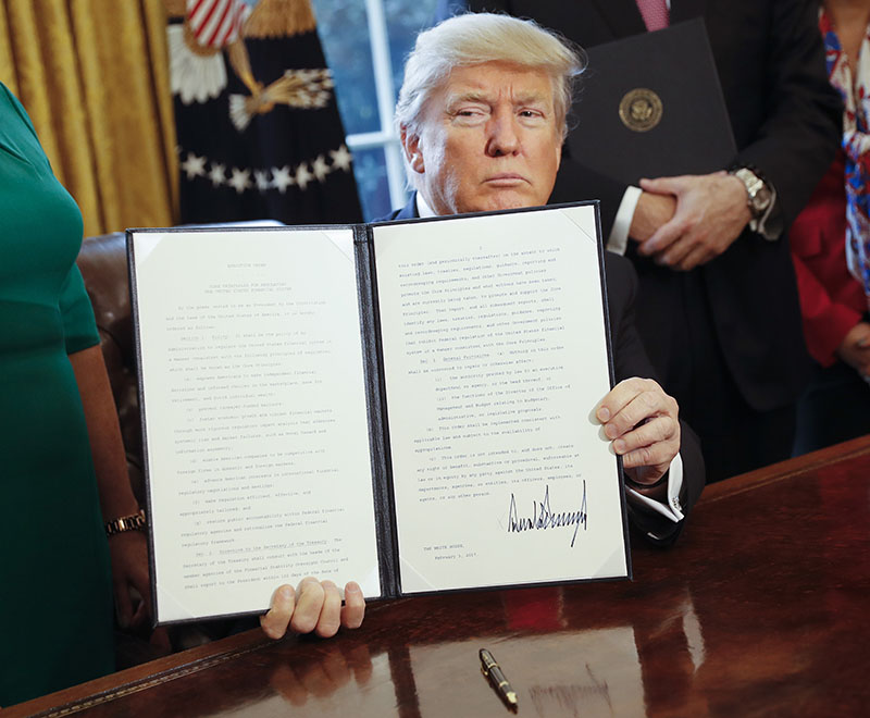 President Donald Trump holds up an executive order after his signing the order in the Oval Office of the White House in Washington, on Friday, February 3, 2017. Photo: AP