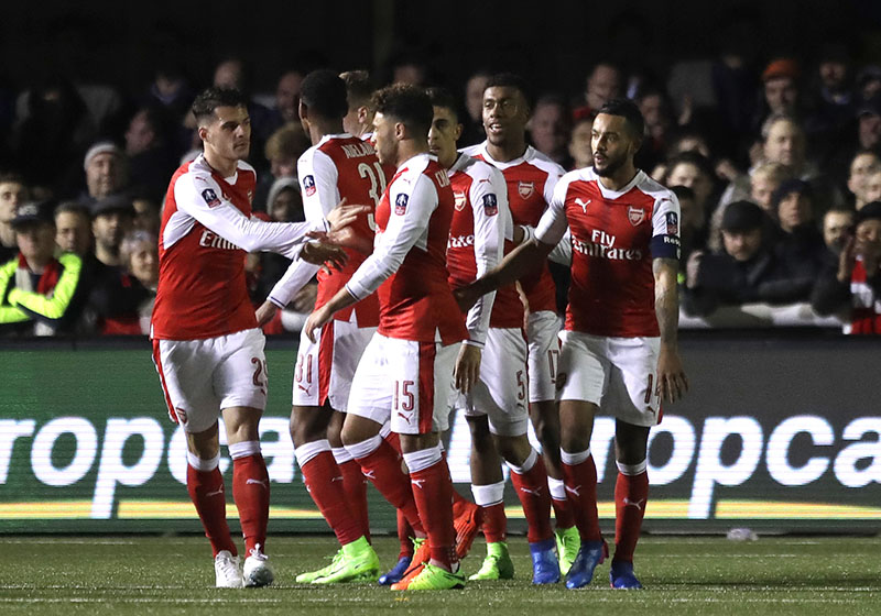 Arsenal's players celebrate Theo Walcott's (right), goal during the English FA Cup fifth round soccer match against Sutton United at Gander Green Lane stadium in London, Monday, February 20, 2017. Photo: AP