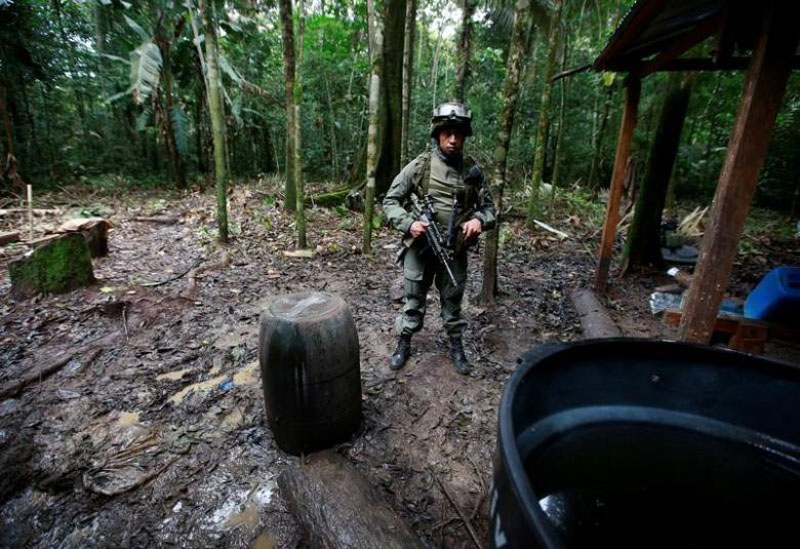 A Colombian anti-narcotics policeman guard a cocaine lab, which, according to the police, belongs to criminal gangs in rural area of Calamar in Guaviare state, Colombia, on August 2, 2016. Photo: Reuters