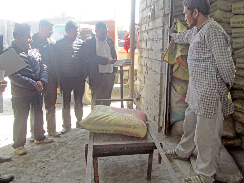 Members of the Kaski District Market Monitoring Committee check weight of a cement sack at a hardware shop during an inspection in Pokhara, on Tuesday, February 7, 2017. Photo: Rishi Ram Baral
