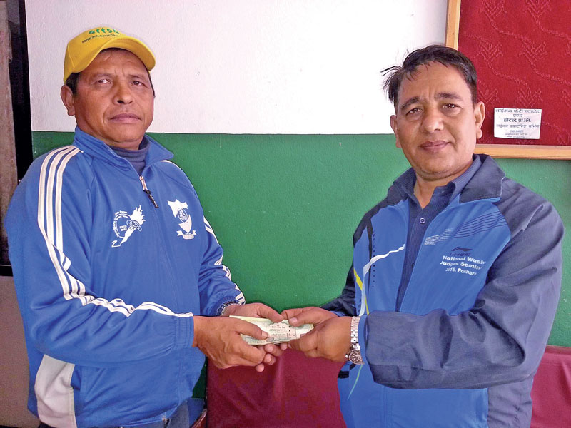 Kaski Coordination Committee of the Nepal Sports Journalists Forum President Keshav Pathak hands over financial assistance to journalist Narayan Shahi on Tuesday, February 21, 2017. Photo: THT