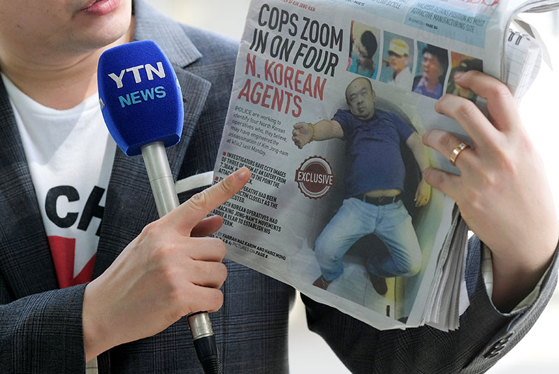 A reporter holds up a local newspaper during his report in front of the morgue at Kuala Lumpur General Hospital where Kim Jong Nam's body is held for autopsy in Malaysia on February 18, 2017. Photo: Reuters