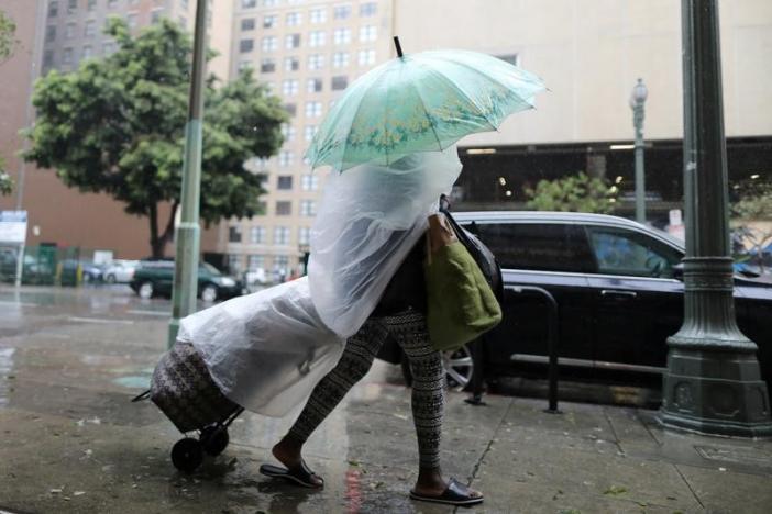 A woman walks through heavy rain in Los Angeles, February 17, 2017. REUTERS/Lucy Nicholson