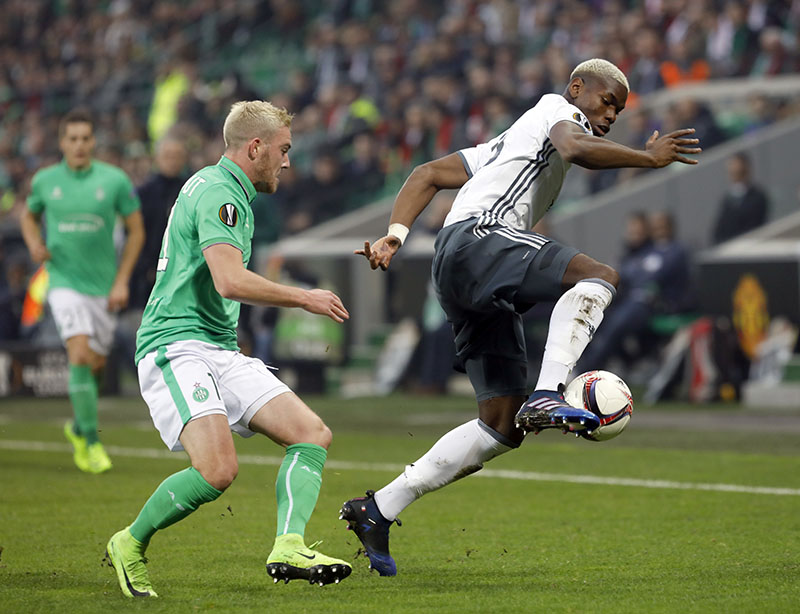 Manchester United's Paul Pogba (right), controls the ball while Saint Etienne's Jordan Veretout looks on during a Europa League round of 32 second leg soccer match between Saint Etienne and Manchester United at Geoffroy-Guichard stadium in Saint Etienne, France, on Wednesday, February 22, 2017. Photo: AP